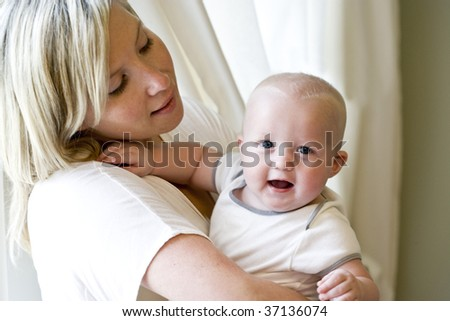 Mother holding happy seven month old baby