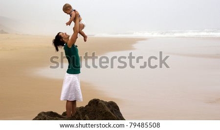 Mother holding her baby in the air whilst standing on a rock on the beach on a overcast day. - stock photo