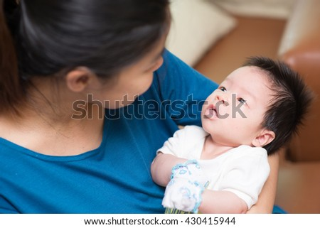 Mother holding her baby looking at face