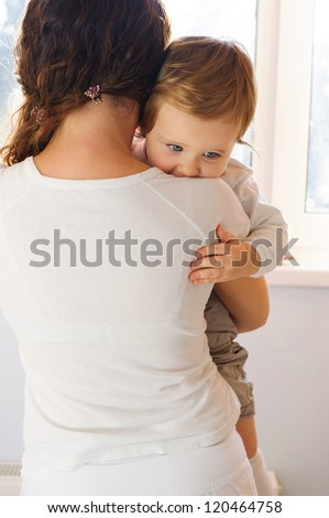 Mother holding her baby near window. Rear view. - stock photo