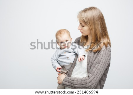 mother holding her baby over white background. The baby looks serious - stock photo