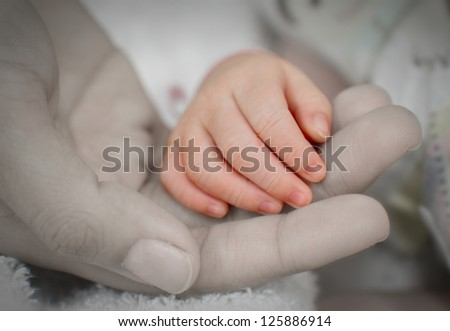Mother holding her baby's hand together,touch of love