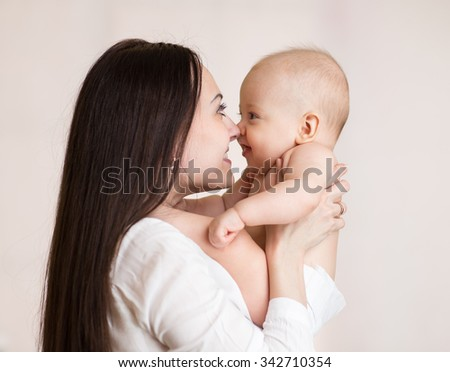 Mother holding her baby son with love - stock photo