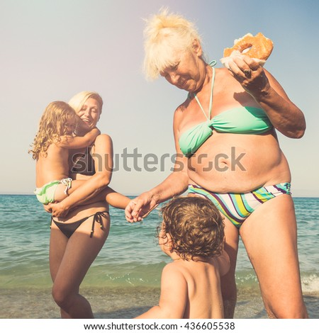 Mother holding her daughter against blue sky and sunshine while second daughter is eating doughnut  - stock photo