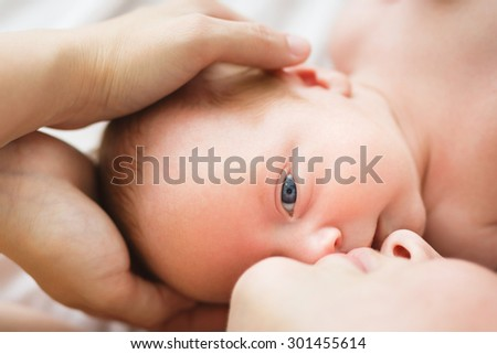 Mother holding her one month old son in studio
