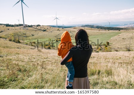 Mother holding her son in nature. Wind turbines in the background.  - stock photo
