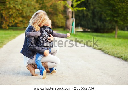 Mother holding her son in the autumn park - stock photo