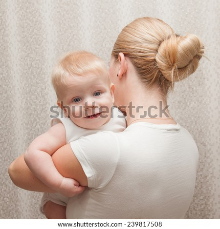 Mother holding his baby. Selective focus on baby head. - stock photo