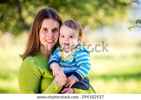 Mother holding little son in her arms, sunny nature