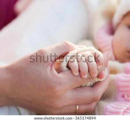 Mother holding newborn baby hand closeup - stock photo
