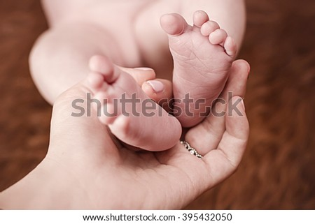 Mother holding newborn daughter feet on a brown background