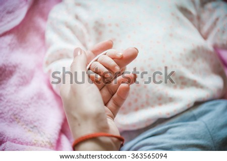 mother holding newborn hands - stock photo