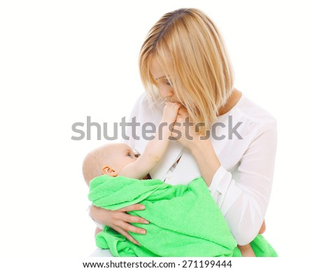 Mother holding on hands baby in towel and kissing