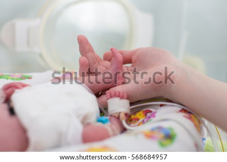 mother holding premature baby legs with a neonatal pulse monitor