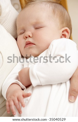 Mother Holding Sleeping Baby In Nursery - stock photo