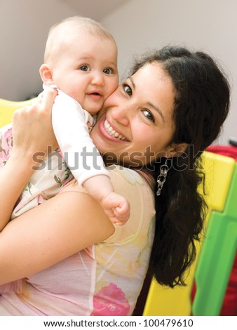 Mother holding small girl in hands and smiling at camera - stock photo