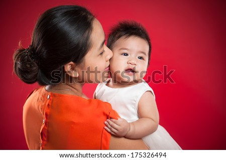 Mother holding sweet baby girl, isolated on red background - stock photo