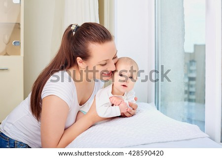 Mother holding sweet baby girl  near the window.