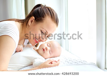 Mother holding sweet baby girl  near the window. - stock photo
