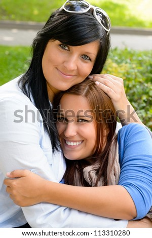 Mother holding teen daughter in her arms happy bonding park - stock photo