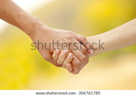 Mother holding the hand of her child. Family love concept - stock photo