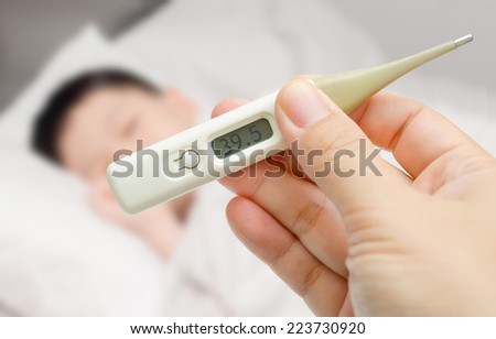 Mother holding thermometer foreground and sick little boy in bed - stock photo