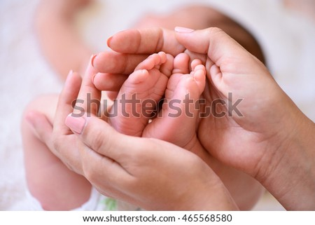 Mother holding tiny foot of newborn baby
