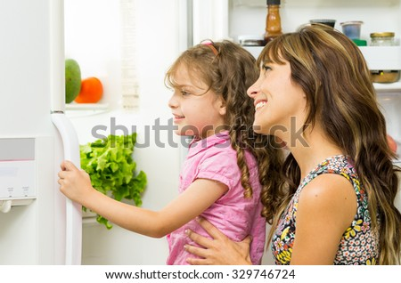 Mother holding up daughter in modern kitchen opening fridge door looking inside happily. - stock photo