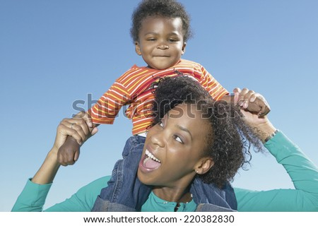 Mother holding young son on shoulders