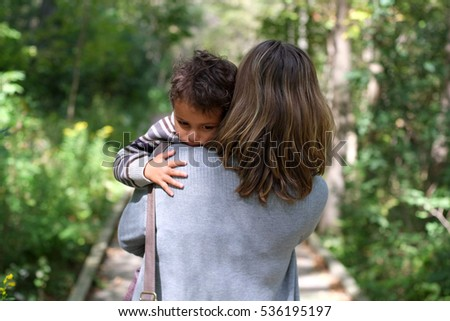 Mother holds and comforts sad little boy