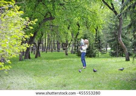 Mother holds daughter on hands on a walk in the Park and kisses her on the cheek, cool weather, full length. - stock photo