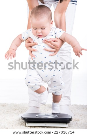 Mother holds her  little baby on a weight scale. - stock photo