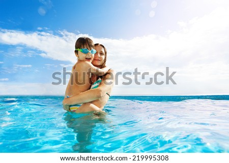 Mother holds her son with goggles, stands in water