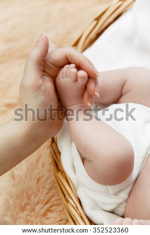 Mother holds little foot of her newborn baby lying in wicker basket - stock photo