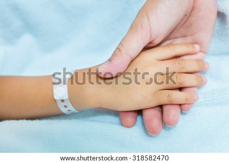 Mother holing boy patient's hands and comforting her - stock photo