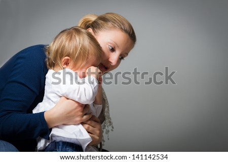 Mother hugging and comforting her little baby girl that is crying. - stock photo