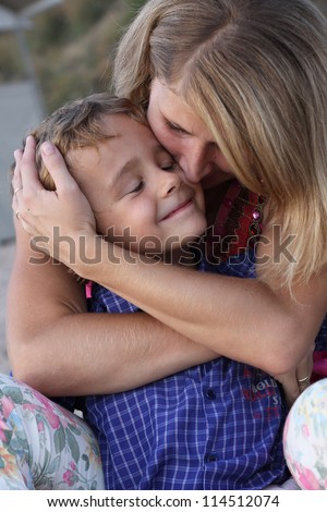 Mother hugging and kissing her baby son - stock photo