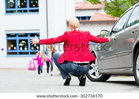 Mother hugging child after bringing her to school - stock photo