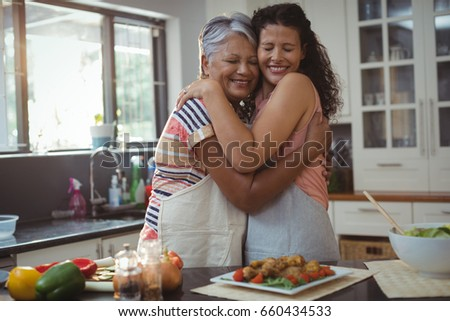 Mother hugging daughter in kitchen at home