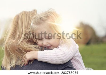 Mother hugging her baby daughter - stock photo