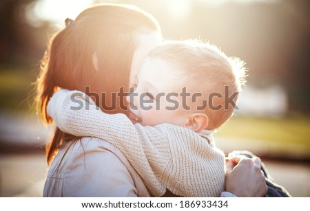 Mother hugging her child during walk in the park - stock photo