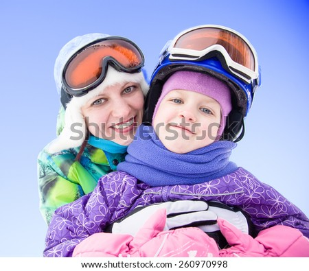 mother hugging her daughter at the ski resort - stock photo