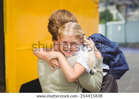 Mother hugging her daughter by school bus outside the elementary school - stock photo