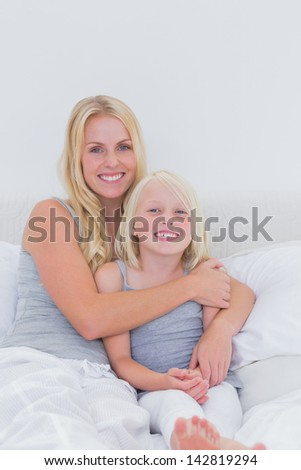 Mother hugging her daughter in bed - stock photo