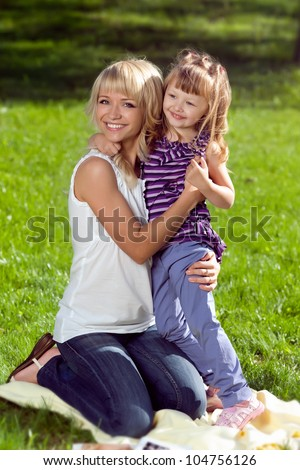 Mother hugging her daughter outdoors in sunny day