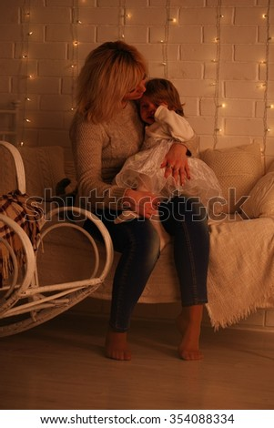 Mother hugging her daughter sitting on the bed - stock photo