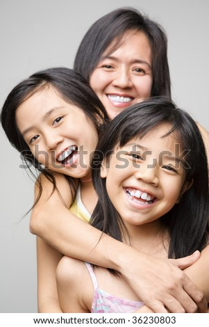 Mother hugging her daughters and posing to camera