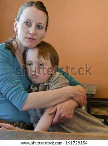 Mother hugging her sad 6-year old son - stock photo