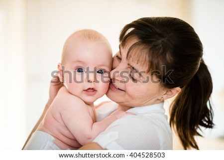 Mother hugging her smiling baby - indoors setting