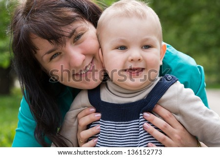 Mother hugging her son and they smile.